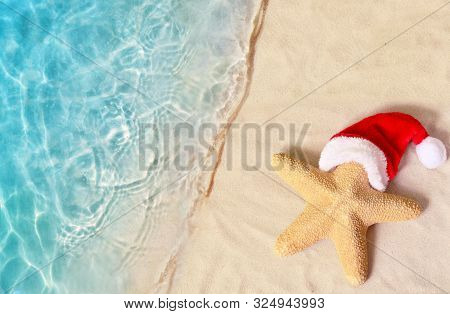 Christmas Holidays Concept. Top View Of Starfish In Santa Claus Hat On Summer Sand Beach