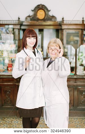 Two Female Pharmacists In Pharmacy. Young Pretty Girl Pharmacist And Middle-aged Woman Pharmacist Sm