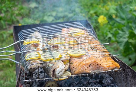Barbecue Outdoors With Grilled Salmon And Gilt-head Bream