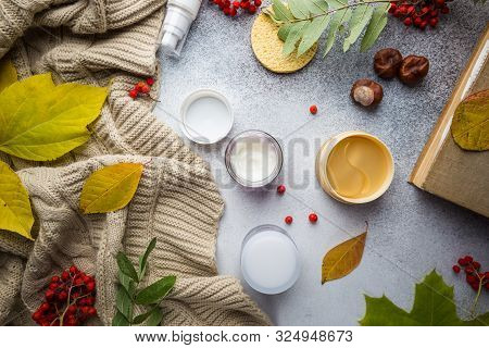 Anti-aging Cosmetic, Cream And Eye Patches On Autumn Background Of Green And Dry Leaves