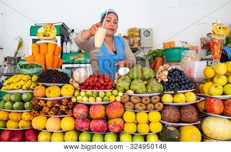SUCRE / BOLIVIA - APRIL 10, 2018: Bolivian woman gives the cup with freshly squizzed juice on the market in the city of Sucre with abundance of fruits on the foreground