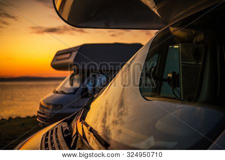 Rv Camper Vans Camping. Two Motorhomes And The Scenic Sunset. Closeup Photo. Summer Vacation On The