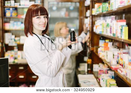 Smiling Attractive Young Lady Pharmacist Holding A Bottle Of Medicines In Her Hand With Focus To Her