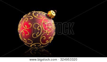 Christmas and New Year Red with gold color Bauble isolated on black background. Holiday bauble decoration. Beautiful Christmas tree ball on black background.
