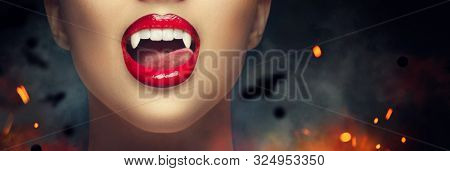 Sexy Vampire Woman's red bloody lips close-up. Vampire girl licking fangs with tongue. Fashion Glamour Halloween art design. Close up of female vampire mouth, teeth. On black scary background with bat