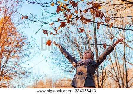 Fall Activities. Middle-aged Woman Throwing Leaves In Autumn Forest. Senior Woman Having Fun Outdoor
