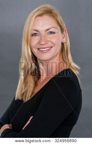 Studio portrait headshot of attractive happy smiling middle aged blonde woman in her thirties or forties