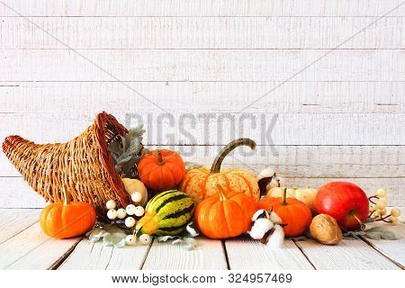 Thanksgiving Cornucopia Filled With Autumn Vegetables And Pumpkins Against A Rustic White Wood Backg