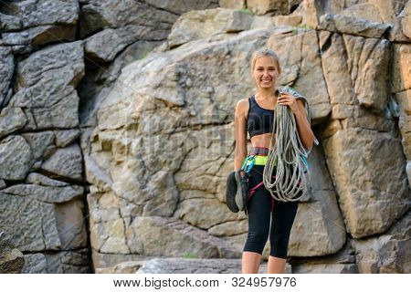 Portrait of Beautiful Smiling Woman Climber Holding the Rope near the High Rock in the Mountains. Adventure and Extreme Sport Concept