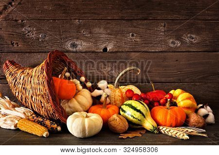 Thanksgiving Cornucopia Filled With Autumn Pumpkins And Vegetables Against A Rustic Dark Wood Backgr