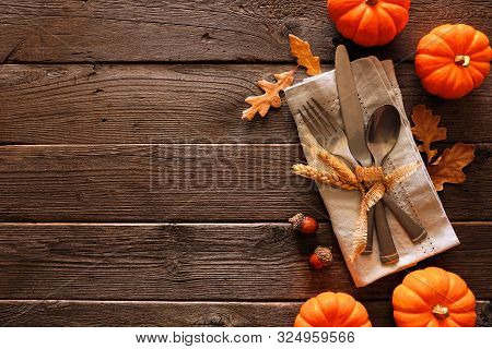 Autumn Harvest Or Thanksgiving Table Scene With Silverware, Napkin, Leaves And Pumpkin Border Agains
