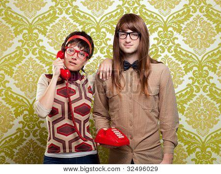 funny nerd humor couple talking retro vintage red telephone on wallpaper
