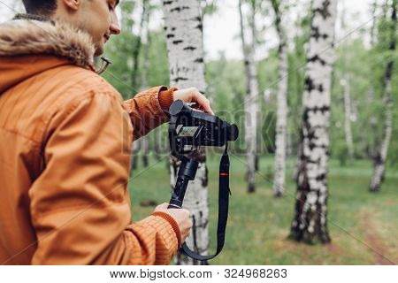Videographer filming spring forest. Man using steadicam and camera to make footage. Video shoot poster