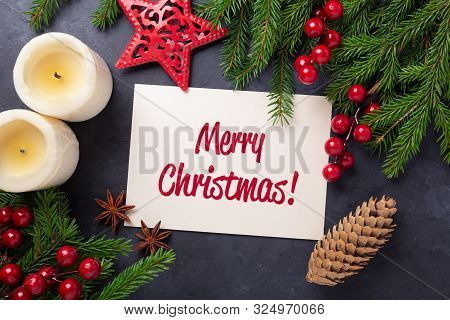 Merry Christmas Card With Paper, Gift Box And Fir Tree Branch On Stone Background. Red And Cold Acce