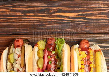Three Fried Hot Dogs On A Dark Wooden Background. Fast Food, Business Lunch. Street Meal. Copy Space