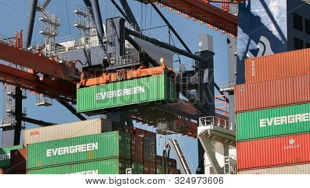 ROTTERDAM, THE NETHERLANDS - SEPTEMBER 21, 2019: Containers being unloaded from a huge cargo ship in the Euromax container terminal of the Port of Rotterdam, busiest port of Europe. Gantry cranes work