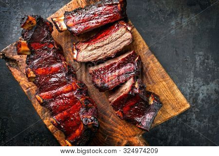 Barbecue chuck beef ribs with hot marinade as top on a wooden cutting board with copy space right