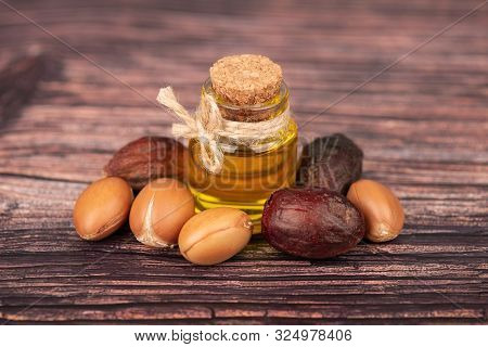 Argan Oil, On Wooden Background. Argan Nuts And Seeds, For Cosmetic And Beauty Products. Natural Arg