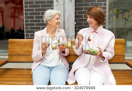 old age, leisure and food concept - senior women or friends eating takeaway salad on city street