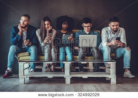 Multicultural Young People Using Laptops And Smartphones Sitting In Row, Diverse African And Caucasi