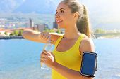 Thirsty fitness woman opens bottle of water after training outdoor. Fit woman using smartphone fitness app on armband as activity tracker. poster