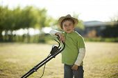 Little boy with lawn mower poster