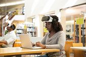 Focused black female student describing VR experience in public library. Woman with taken off virtual reality glasses, sitting at desks and using laptop. VR experience concept poster