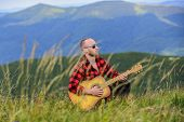 Man with guitar on top of mountain. Acoustic music. Summer music festival outdoors. Playing music. Sound of freedom. Inspired musician play rock ballad. Compose melody. Inspiring environment poster