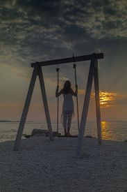 Peroj, Croatia - August 30, 2019: Unidentified Girl Standing And Resting On A Swing Near The Sea At