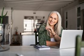 Portrait of happy senior woman holding eyeglasses and looking at camera at home. Successful old lady laughing and working at home. Beautiful stylish elderly woman smiling and relaxing at home.