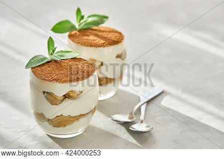 Classic Dessert Tiramisu In A Glass On A Table On A Sunny Day.
