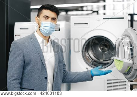 Male Shop Assistant In Medical Mask Demonstrates A New Model Of Washing Machine In Hypermarket