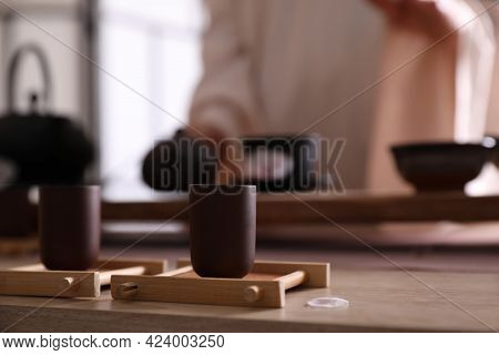 Master Conducting Traditional Tea Ceremony At Table Indoors, Focus On Cup