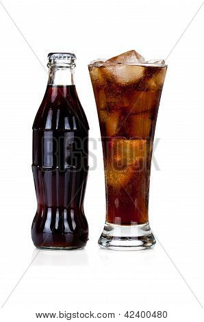 Bottle Of Cola With Glass Full Of Soda And Ice On White