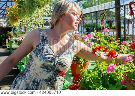 Florists Woman Working With Flowers At A Greenhouse.