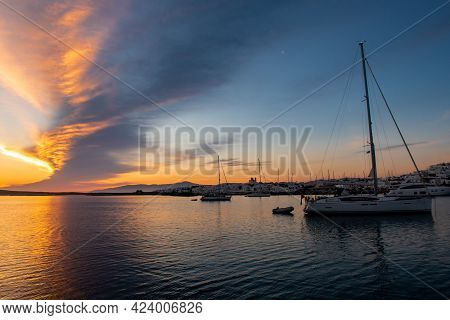 Anchored Sailboats With Magnificent Sunrise With Saturated Orange And Purple Bank Of Clouds In The S