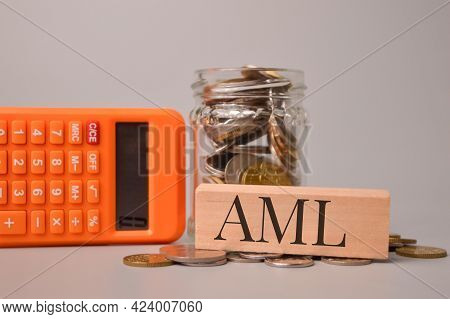 Calculator, Stack Of Coins And Wooden Block With Text Aml Stands For Anti - Money Laundering