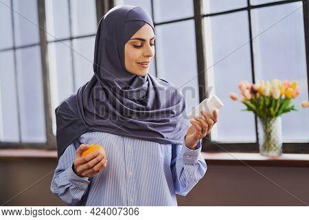 Arabian Female Health Blogger Holding An Orange And A Bottle Of Pills