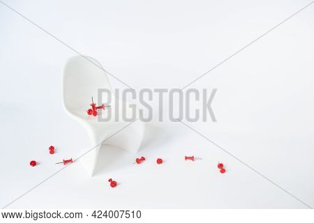 White Chair With A Red Paper Pin On A White Background. Hemorrhoids Concept