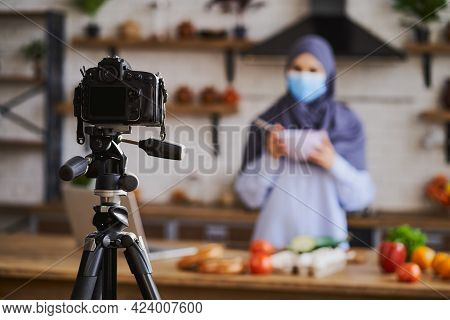 Camera On A Tripod In Front Of A Muslim Woman Cooking A Meal