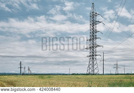 Power Lines High Voltage , Landscape On A Green Field At Noon, Bright Sunny Day, Blue Sky With Cloud