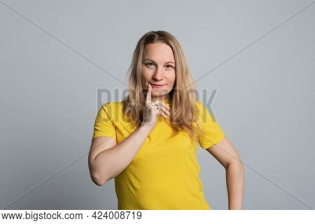 Confused Mature Woman Wearing Basic Yellow T Shirt Looking At Camera With Pensive Look. Studio Shot,