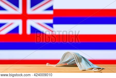 A Medical Mask Lies On The Table Against The Background Of The Flag Of Hawaii. The Concept Of A Mand