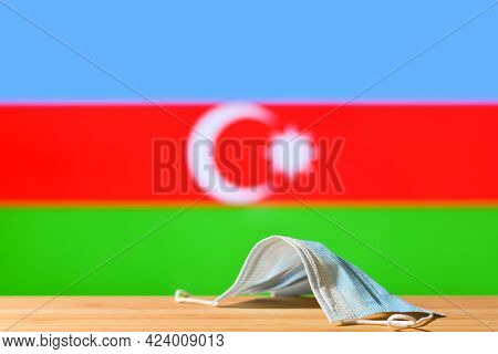 A Medical Mask Lies On The Table Against The Background Of The Flag Of Azerbaijan. The Concept Of A