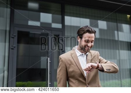 Happy Bearded Businessman In Suit Looking At Wristwatch