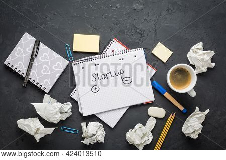 Startup concept - Notepad, coffee, discarded ideas and writing tools on black desk