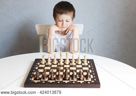 A Cute Boy Of Caucasian Appearance Sits In Front Of A Table With A Chessboard. Games For Logic And S