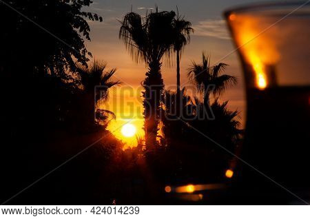 Blurred Glass Of Turkish Tea In The Foreground Against Sunset Behind Silhouettes Of Palm Trees. Beau