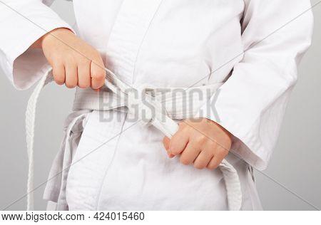 Children's Sports. Karate. Children's Hands Tying A White Karate Kimono Belt