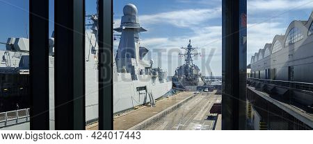 Gdynia - Poland - 2021: An Italian Frigate And An American Destroyer Moored At A Seaport Wharf